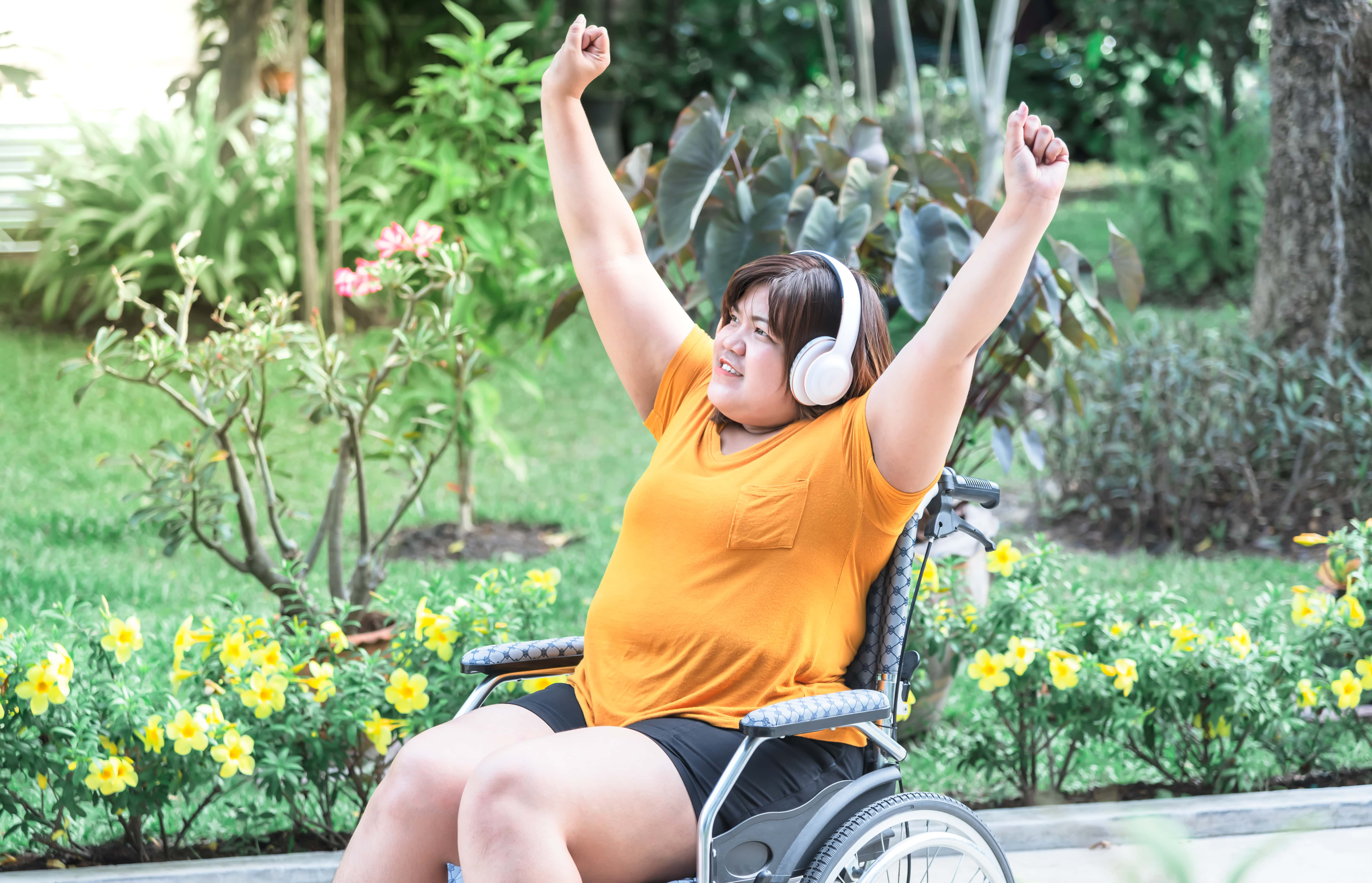 Young woman in a wheelchair with headphones on and arms raised in the air in triumph