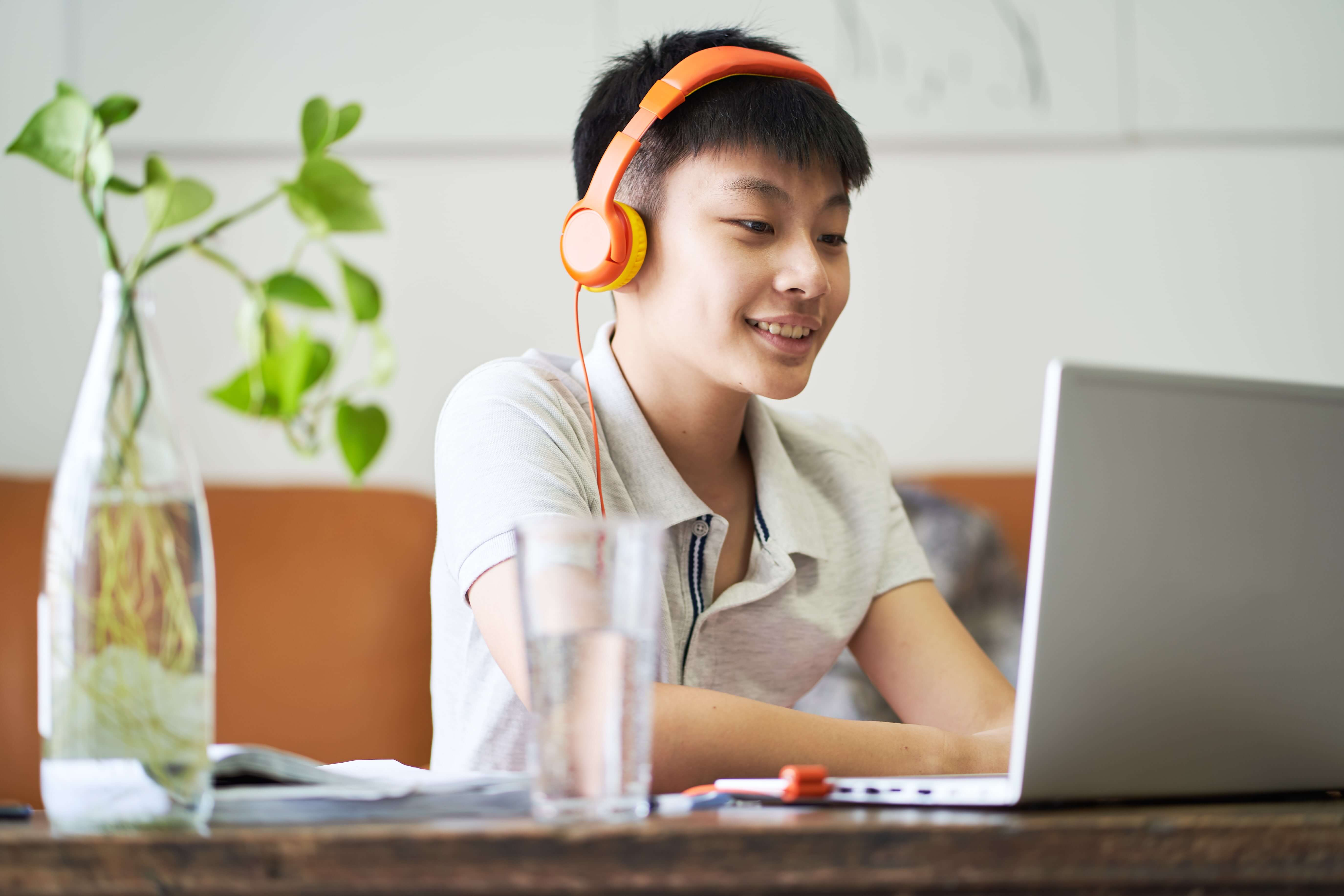 Asian teenage boy wearing headphone and working on a laptop computer
