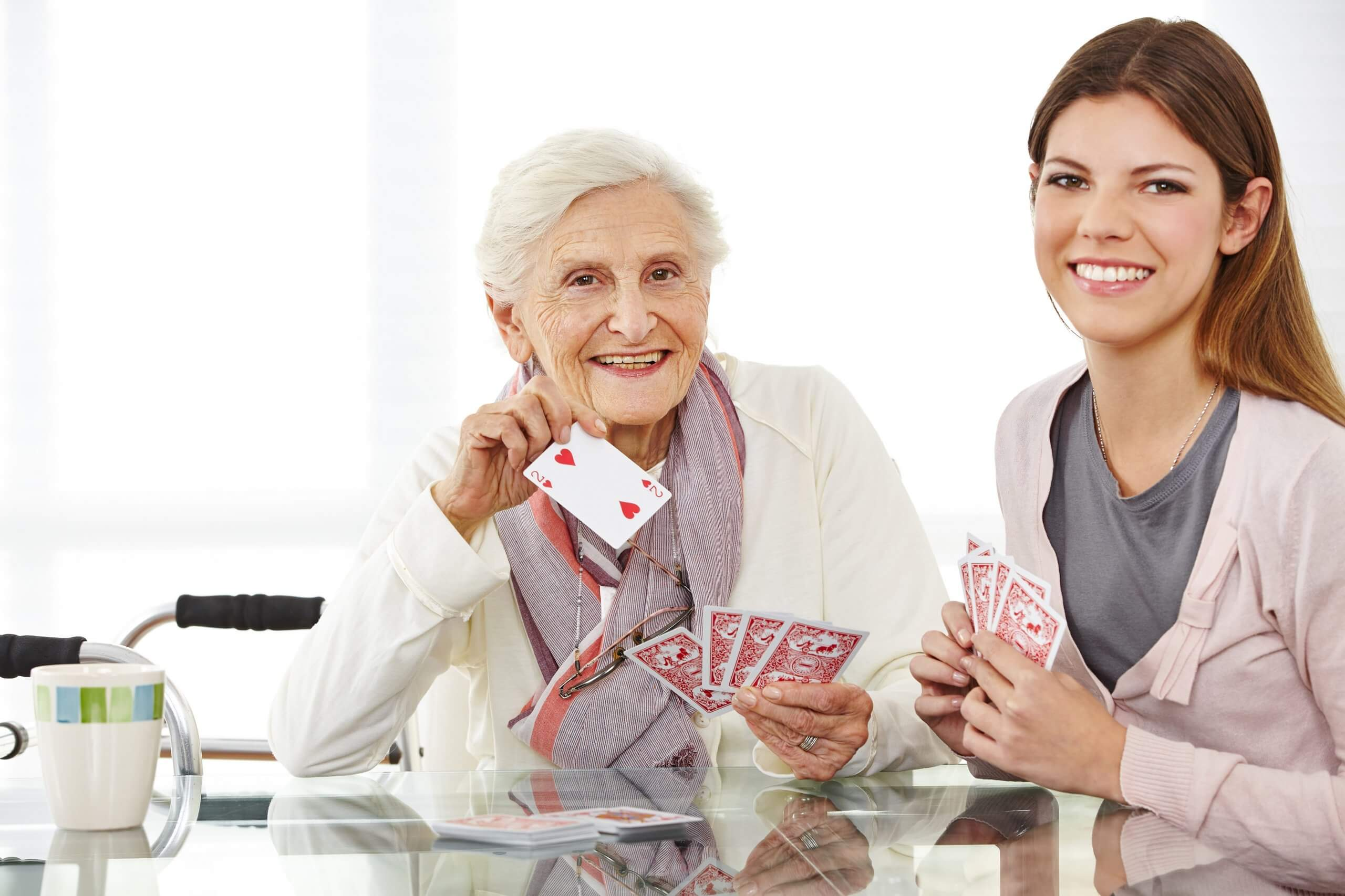 Care worker playing cards with elderly woman