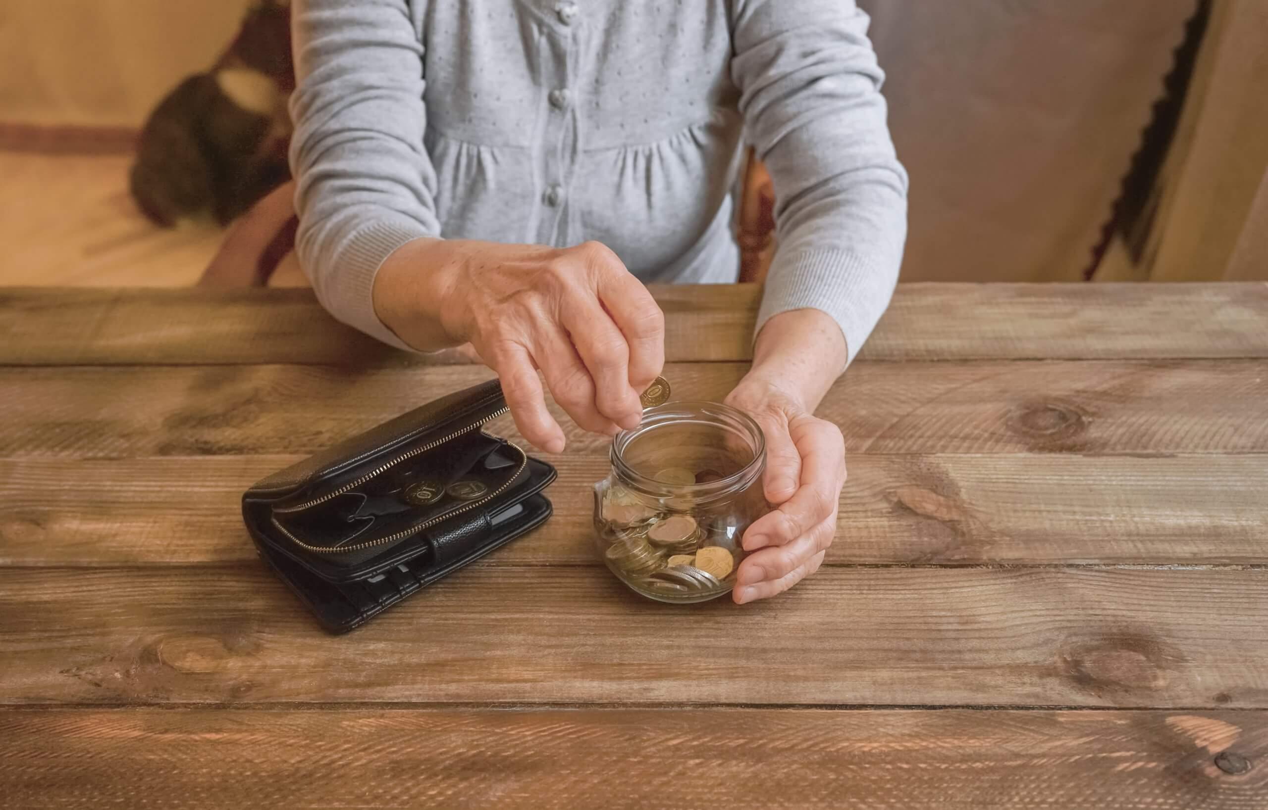 Elderly hands placing coins in a jar